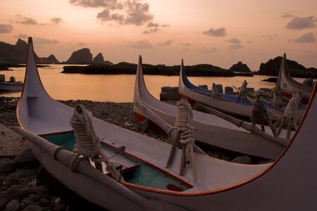 Traditional boats at sunrise.  This is in Taiwan and the boats belong to an ethnic group there.  photo