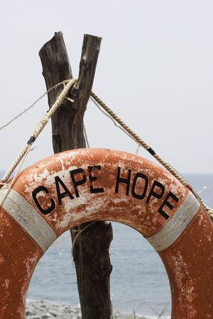 life saving: A photo of an old life saving ring at the beach. The ring has the words cape hope on it.