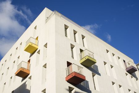 A modern apartment block, with a simple design, bright colors and balconies.  This is high density housing with a view for urban beauty.