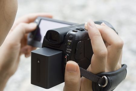 A young woman is using a video camera to record something. Stock Photo