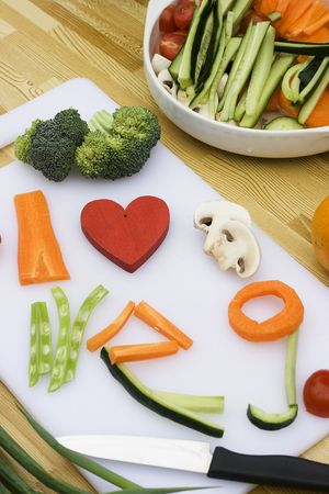 veg: Vegetables have been used to spell Veg.  Carrots, beans, cucumbers, tomatoes, mushrooms and broccoli are the vegetables.  A red wooden heart has been used for love. Stock Photo