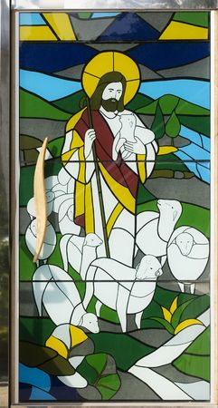 Stained glass image of Jesus with a lamb.  Like a sheppard taking care of his flock.  This is on a door, like a door to heaven, Stock Photo