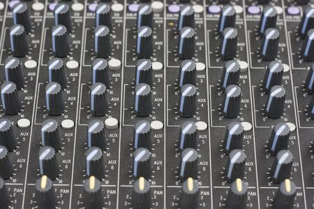 remix: Close up of a sound mixer being operated.  The machine has been checked for brand names and logo and have been removed.