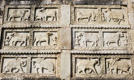 A carving in stone of elephants, cows and horses.  This was taken at an Indian palace and probably depicts the role of animals in royal India. photo