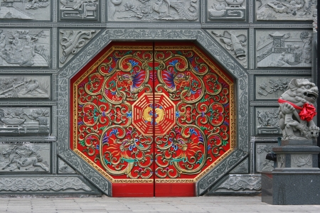 Traditional Chinese style door at a temple. This door has eight sides and is red in color.  It is decorated in traditional Chinese style.