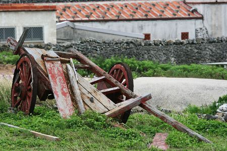 discarded: An old discarded cart in a rural scene with farming buildings in the background.  Stock Photo