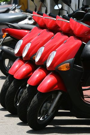 holiday destination: A row of red scooters.  These scooters are for hire at a holiday destination. Stock Photo