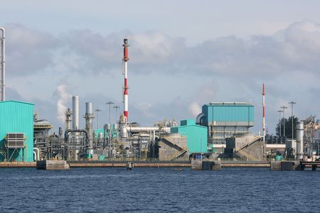 An oil refinery on the coast.  This industrial looking building is located near a port.  There is some gas being released. photo