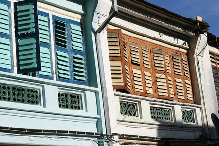 These are colorful colonial houses in Penang, Malaysia.  They are over a hundred years old and are bright and colorful.  They are typical of old houses in George Town.  Stock Photo
