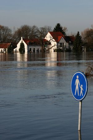 No school today!  A river has flooded its bank and a houserestaurant.  Theres a sign with a adult and a child on it and this is deep under water.