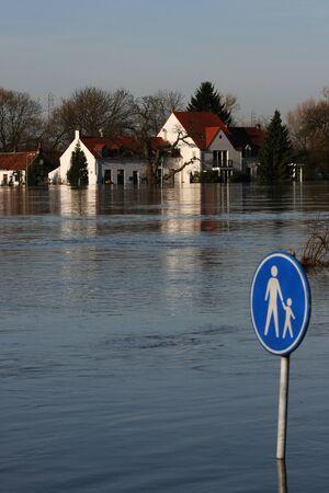Keine Schule heute!  Ein Fluss hat seine Bank und ein Haus/Restaurant überschwemmt.  Es gibt ein Zeichen mit einem Erwachsenen und ein Kind auf es und dies ist tief unter Wasser.