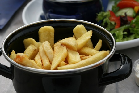 Chips or French fries in a pot and served with a meal.