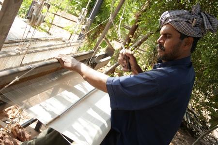 gujarat: 7th Dec 2007, near Bhuj, Gujarat, India.  A man working on a loom.  He