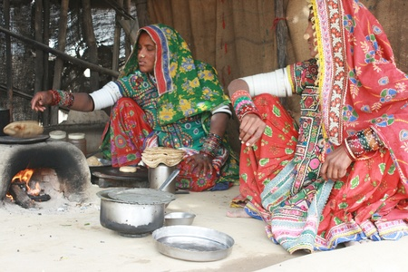 mujeres cocinando: Rann de Kutch, Gujarat, India, diciembre 26, 2007, dos mujeres que cocinan los alimentos tribal con cocina tradicional