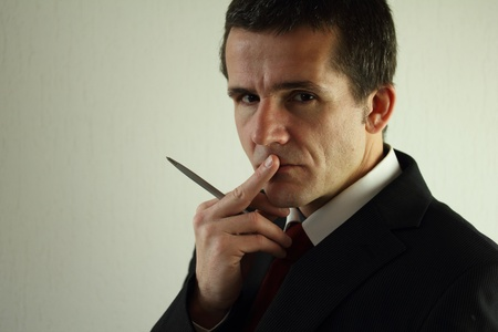A business man thinking over an idea   He s in deep thought   He s holding a pen