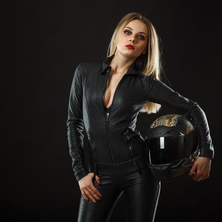 biker girl posing in studio in black background Фото со стока