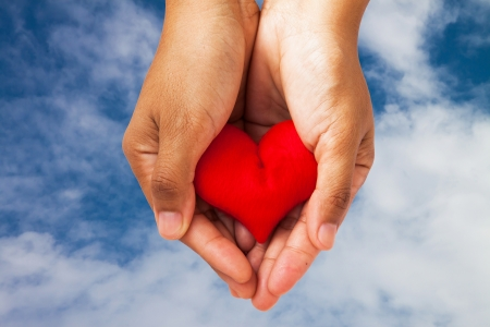Red heart on hands on blue sky background photo