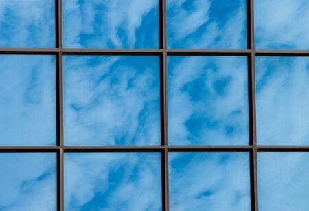 Cloudy sky reflected in the glass wall photo