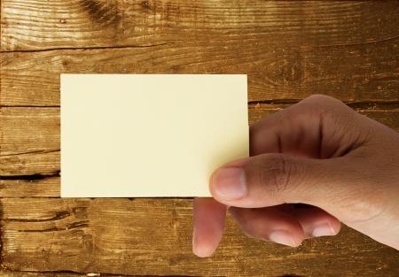 carta identit�: Mano che tiene scheda in bianco su sfondo di legno del grunge Archivio Fotografico