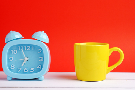 Colorful alarm clock and yellow cup on white wood table and red background concept. Close up and blank space.