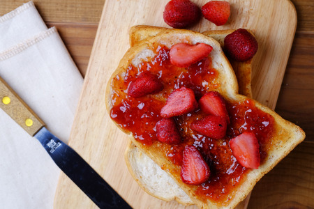whole wheat toast: Strawberrie jam on grain bread isolated on wooden background, top view and selective focus.