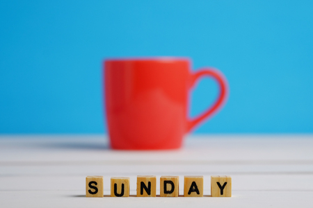Close up of Sunday in letter wooden block selective focus on white wood table and blue background concept. Red cup decoration style. Stock Photo