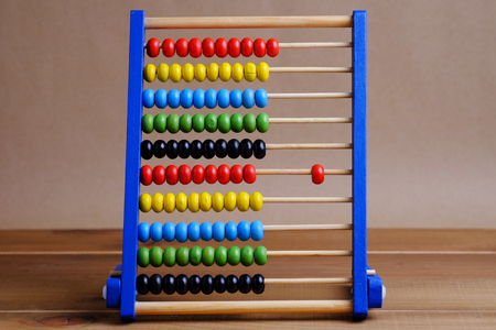 sums: Close up colorful abacus, traditional abacus in front of  wooden background.
