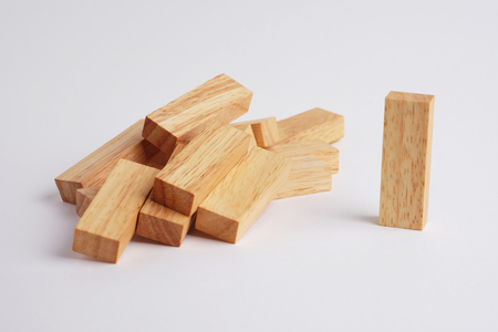 dominant: One wooden block standing and outstanding among the collapse of fall in line, business concept able to survive or dominant from destruction. Selective focus on gray background. Stock Photo