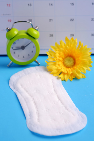 critical care: Woman hygiene protection of sanitary pad on blue background, woman menstruation cycle, critical day and selective focus.