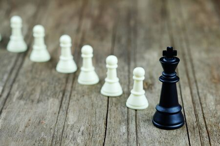 Close up of chess with black king on wood background concept. Business concept able to survive or dominant from competition, leadership and activation. Selective focus and vintage style. Stock Photo