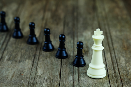 Close up of chess with white king on wood background concept. Business concept able to survive or dominant from competition, leadership and activation. Selective focus and vintage style. Stock Photo