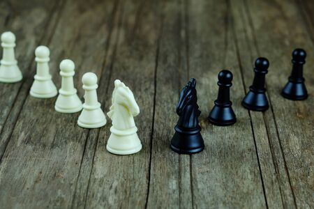 Close up of white and black minor piece chess on wood background concept. Business concept of between competition, individuality, confrontation. Selective focus and position space.