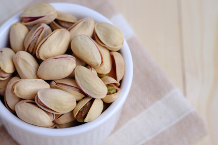 Close up of pistachio nut in cup on wooden background. Selective focus and blank space concept. Stock Photo