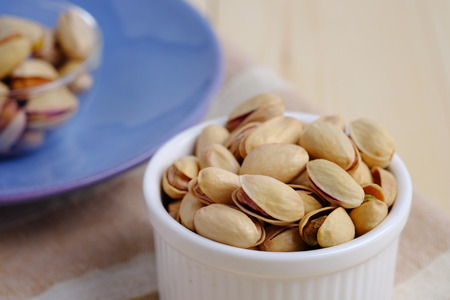 Close up of pistachio nut in cup on wooden background. Selective focus, decorated and blank space concept.