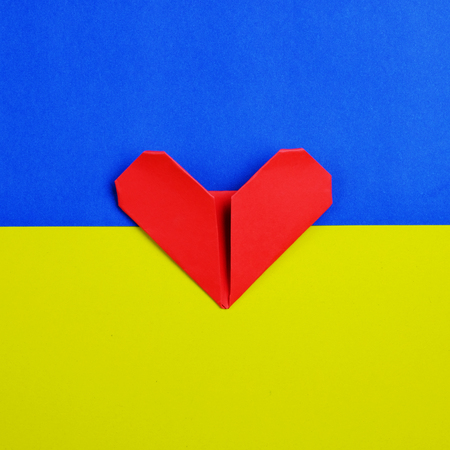 Top view of one red heart paper on blue and yellow background idea, selective focus, valentine day.