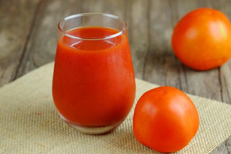 Schließen Sie oben vom gesunden Tomatensaft im Glas auf hölzernem Tabellenhintergrund, gesundem Getränk, selektivem Fokus und kopieren Sie Raum.