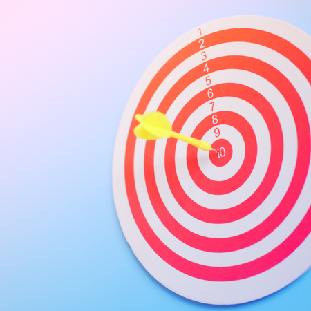 Close up of Target dart board with dart arrow on blue background. Business and education concept metaphor to target is to expect, copy space and selective focus. Stock Photo