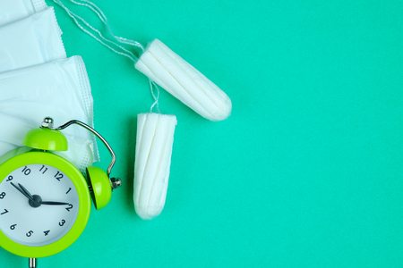 Woman hygiene protection of cotton tampons and sanitary pad on green background, woman menstruation cycle, critical day, selective focus and copy space. Zdjęcie Seryjne