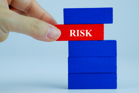 survive: Close up of Business concept red wooden block with risk letter in hand. Business concept for process teamwork and risk success process.