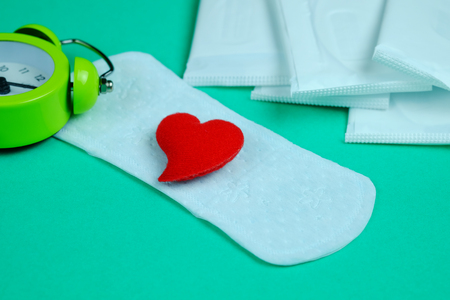 critical care: Woman hygiene protection of sanitary pad on green background. Woman menstruation cycle, critical day, selective focus and copy space.