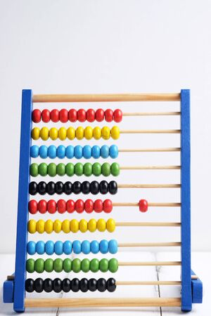 sums: Close up of colorful abacus, traditional abacus in front of white background, selective focus. Stock Photo