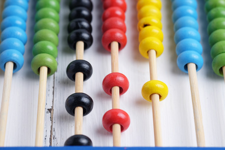 sums: Close up of colorful abacus, traditional abacus in front of white wood background, selective focus. Stock Photo