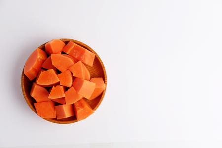 회색 배경에 나무 접시에 달콤한 파파야 조각의 상위 뷰. 빈 공간 및 선택적 포커스입니다.