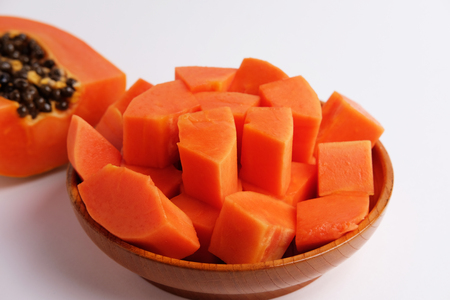 Close up of sweet papaya slices in wood plate on gray background. Blank space and selective focus.