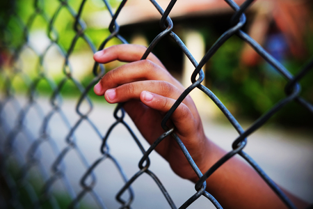 Hand in jail with girl and house of detention concept, vignette effect and selective focus. 스톡 콘텐츠
