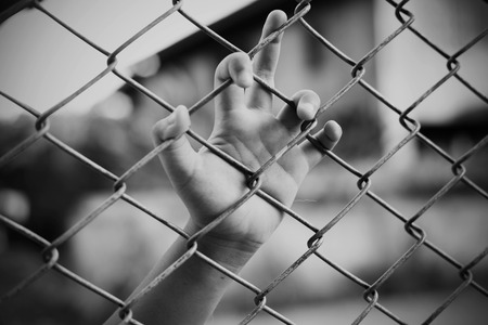 Hand in jail with girl and house of detention concept, vignette effect and selective focus, black and white tone.