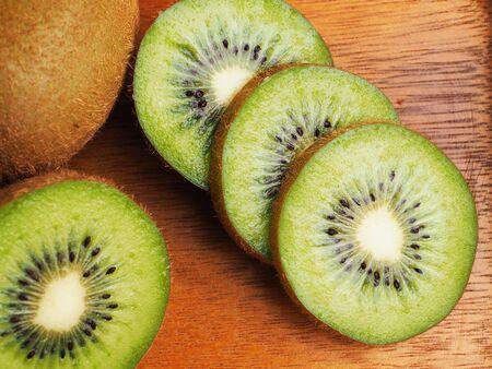 Kivi fruit close up on wood background.