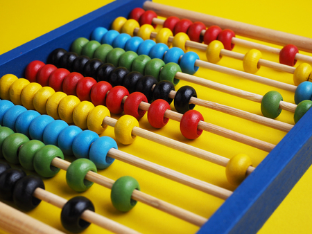 Close up colorful abacus, traditional abacus in front of  yellow background concept, selective focus. Stock Photo