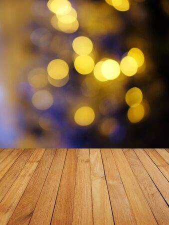 Wood decking with image of abstract bokeh background of resturant lights concept, space for text.