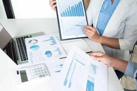 Zwei Unternehmerinnen diskutieren die Diagramme und Grafiken, die die Ergebnisse zeigen. Standard-Bild
